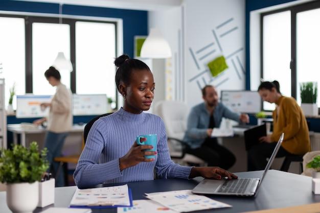 Une femme d'affaires africaine tenant une tasse de café, un briefing du projet de lecture sur le lieu de travail de démarrage. équipe diversifiée d'hommes d'affaires analysant les rapports financiers de l'entreprise à partir d'un ordinateur.