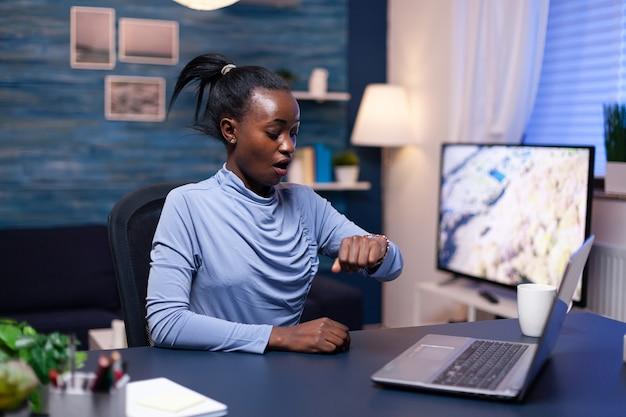 Femme d'affaires africaine vérifiant l'heure en regardant la montre-bracelet travaillant tard à la date limite du bureau à domicile. gestionnaire noir nerveux faisant des heures supplémentaires en travaillant sur ordinateur.