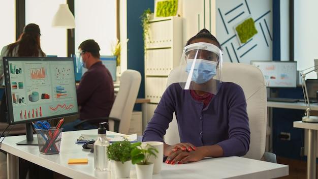 Femme d'affaires africaine avec visière et masque parlant à la caméra ayant une réunion vidéo avec des partenaires distants. point de vue d'une femme parlant avec l'équipe lors d'une conférence en ligne pendant que des collègues travaillent en arrière-plan