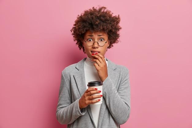 Femme d'affaires afro-américaine adulte inquiète étant en difficulté, a fait un énorme désordre au travail, mord les lèvres, semble maladroite, tient une tasse de café jetable, porte des vêtements formels