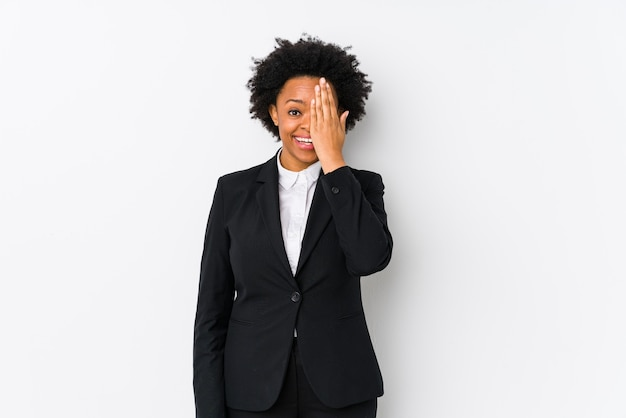 Femme d'affaires afro-américaine d'âge moyen sur blanc isolé s'amusant couvrant la moitié du visage avec la paume.