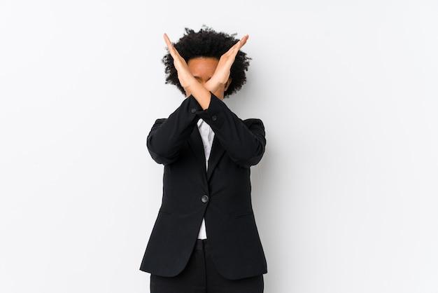 Femme d'affaires afro-américaine d'âge moyen contre un mur blanc en gardant deux bras croisés