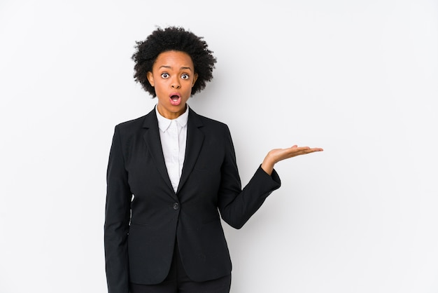 Femme d'affaires afro-américaine d'âge moyen contre un mur blanc isolé impressionné tenant copie espace sur la paume.