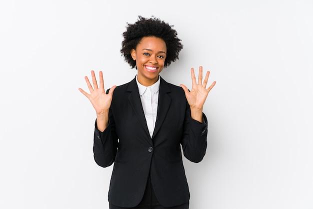 Femme d'affaires afro-américaine d'âge moyen contre un mur blanc isolé montrant le numéro dix avec les mains.