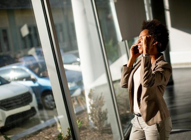 Femme d'affaires afro-américaine à l'aide de téléphone mobile par la fenêtre dans le bureau aux beaux jours