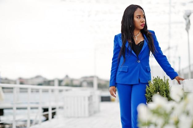 Femme d'affaires afro-américaine au costume bleu posé.