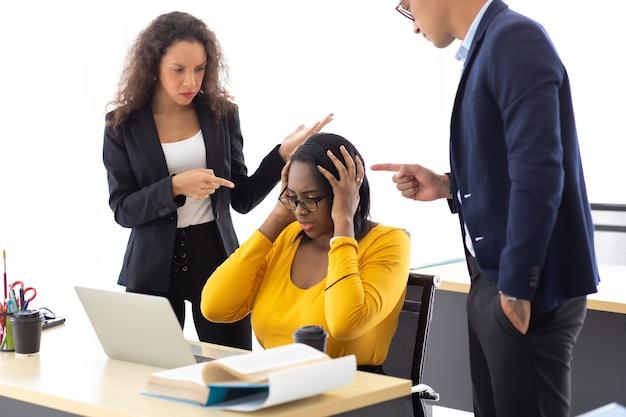 Une femme d'affaires afro-américaine a bouleversé une erreur grave et un mauvais travail. des collègues hommes et femmes intimidant et blâmant une associée en la pointant du doigt