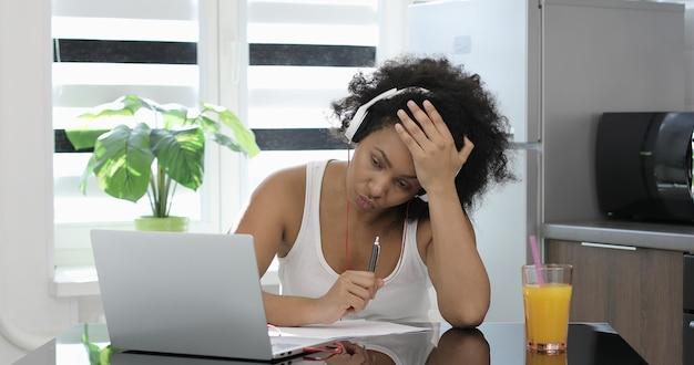 Femme d'affaires afro-américaine fatiguée portant des écouteurs communiquant par appel vidéo