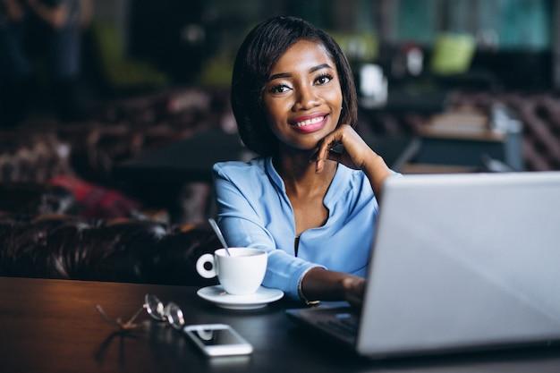 Femme d'affaires afro-américaine avec ordinateur portable dans un café