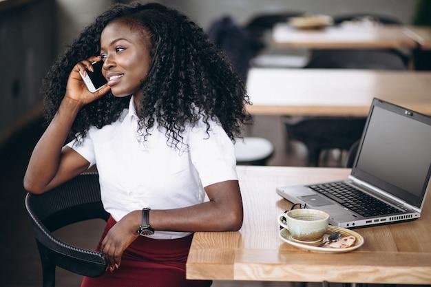 Femme d'affaires afro-américaine parlant au téléphone dans un café