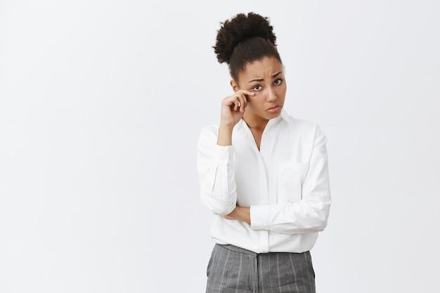 Femme d'affaires afro-américaine sombre et triste sanglotant, pleurant et essuyant la larme de l'oeil