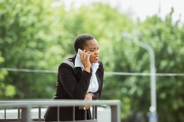 Femme d'affaires afro-américaine en tenue de bureau souriant, semble confiant et heureux, occupé