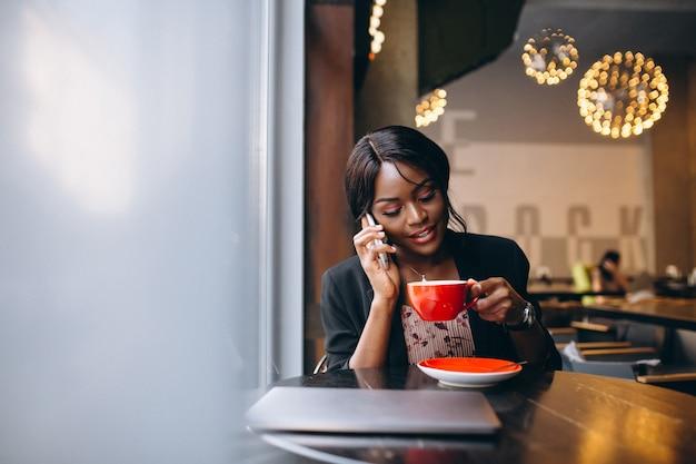 Femme d'affaires afro-américaine travaillant dans un café