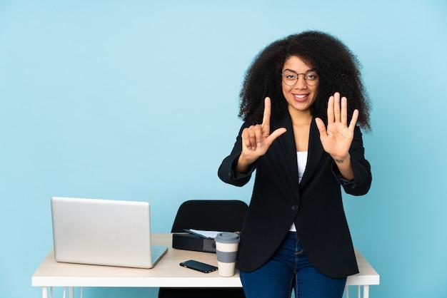 Femme d'affaires afro-américaine travaillant dans son lieu de travail en comptant sept avec les doigts