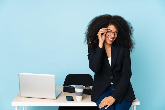 Femme d'affaires afro-américaine travaillant dans son lieu de travail avec des lunettes et heureux