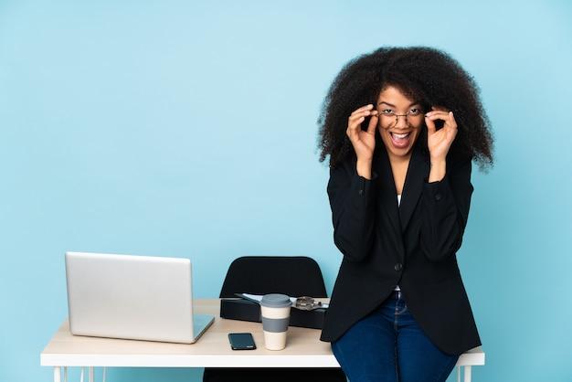 Femme d'affaires afro-américaine travaillant dans son lieu de travail avec des lunettes et surpris