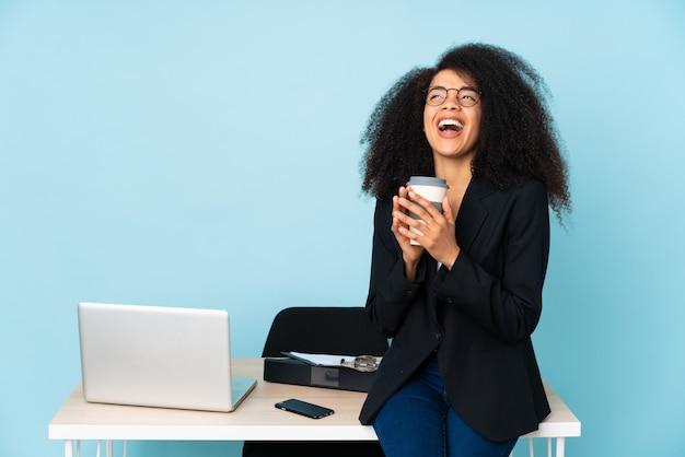 Femme d'affaires afro-américaine travaillant sur son lieu de travail complotant quelque chose