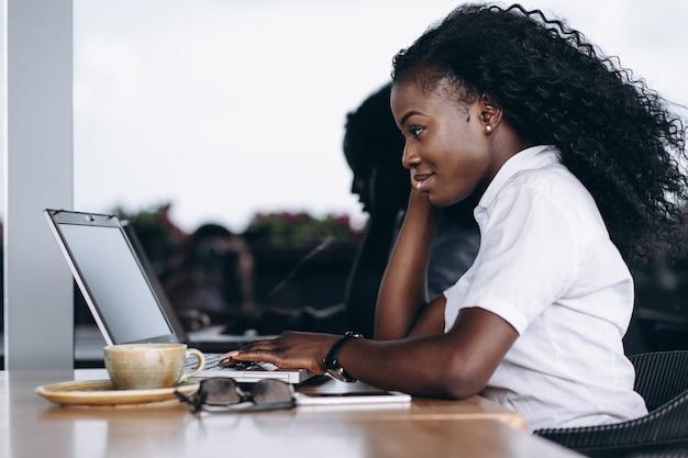 Femme d'affaires afro-américaines avec ordinateur et téléphone dans un café