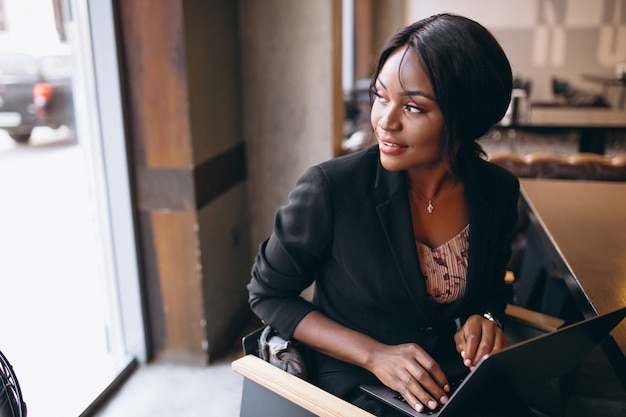 Femme d'affaires afro-américaines travaillant sur un ordinateur dans un bar