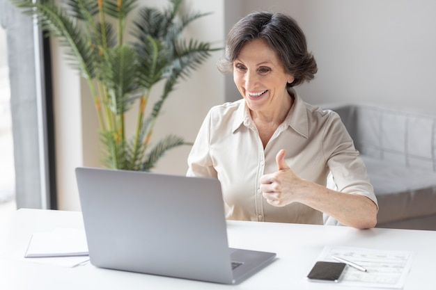 Une femme d'affaires d'âge caucasien agite la main, salue les participants à la vidéoconférence, utilise un ordinateur portable pour communiquer en ligne assis au bureau ou à la maison. appel vidéo, concept de travail à distance