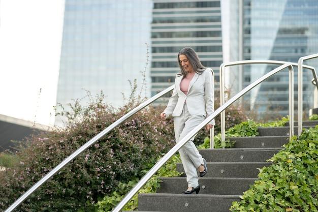 Femme d'affaires d'âge moyen descendant les escaliers