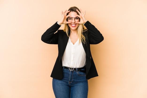 Femme d'affaires d'âge moyen isolée sur beige montrant un signe correct sur les yeux