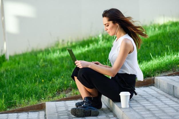 Femme d'affaires d'âge moyen travaillant avec son ordinateur portable assis sur le sol.