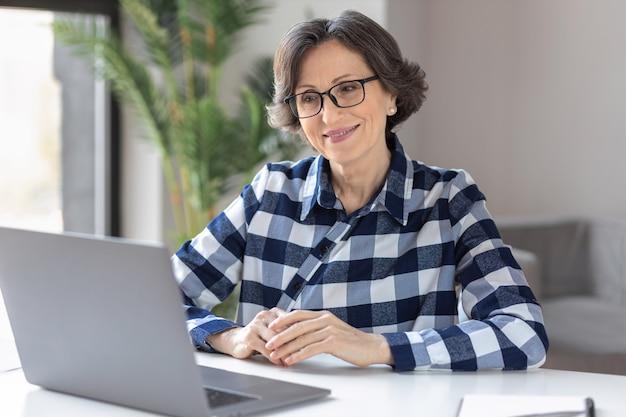 Femme d'affaires âgée caucasienne réussie utilisant un ordinateur portable assis sur le lieu de travail au bureau à domicile. travail à distance