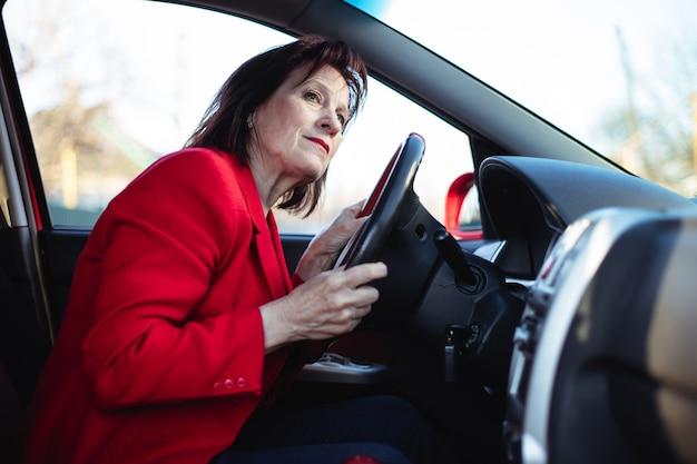 Une femme d'affaires âgée conduit sa voiture. jette un œil sur la route principale