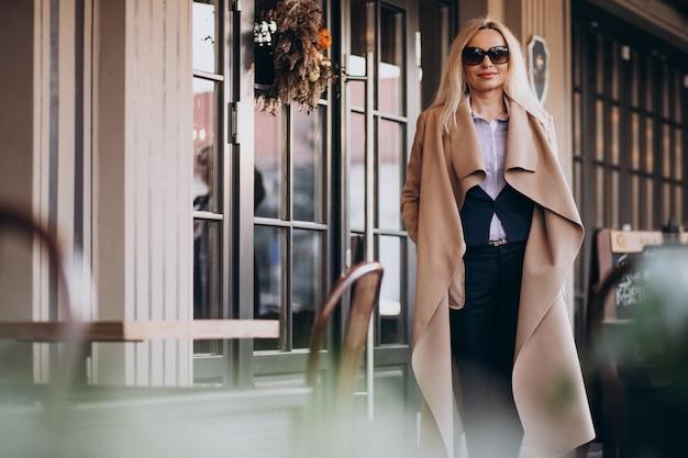 Femme d'affaires âgée dans un manteau à l'extérieur du café