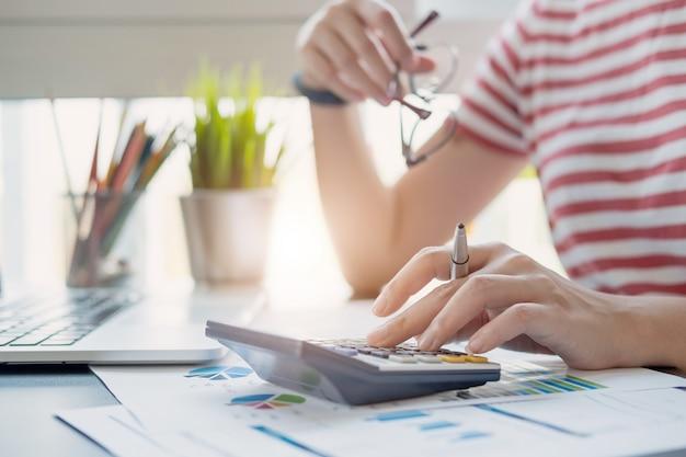 Femme d'affaires à l'aide d'une calculatrice et d'un ordinateur portable pour faire des finances mathématiques sur un bureau en bois