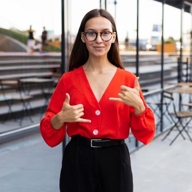 Femme d'affaires à l'aide de la langue des signes à l'extérieur au travail