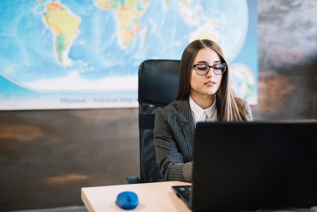 Femme d'affaires à l'aide d'un ordinateur portable à la table