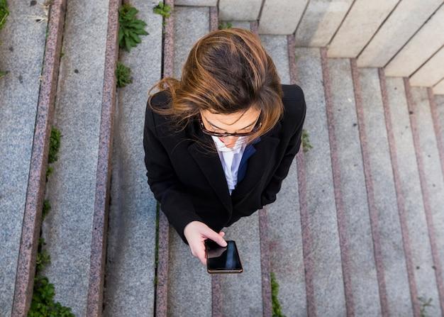Femme d'affaires à l'aide de smartphone dans les escaliers