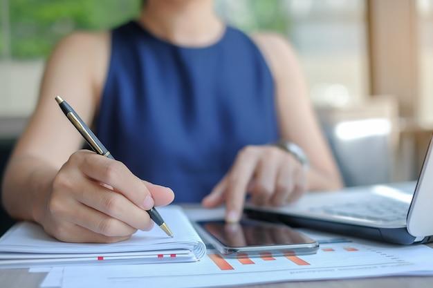 Femme d'affaires à l'aide de smatphone pour l'analyse du plan marketing