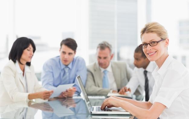 Femme d'affaires à l'aide de son ordinateur portable lors d'une réunion en regardant la caméra