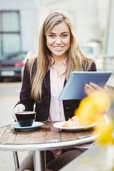 Femme d'affaires à l'aide de son tablet pc au café