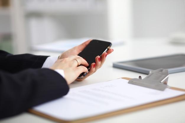 Femme d'affaires à l'aide de son téléphone au bureau, assis sur un bureau