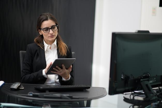 Femme d'affaires à l'aide d'une tablette dans son bureau d'entreprise, concept de carrière de femme d'affaires