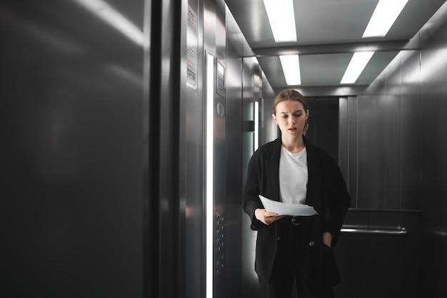 Une femme d'affaires ambitieuse et réfléchie se tient dans l'ascenseur et essaie de se souvenir de quelque chose.