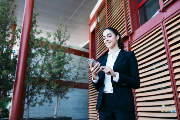 Femme d'affaires amicale avec smartphone