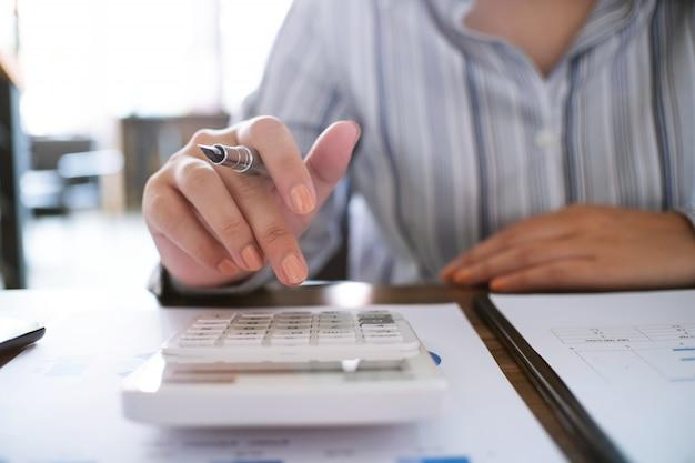 Femme d'affaires en analysant les graphiques d'investissement avec la calculatrice