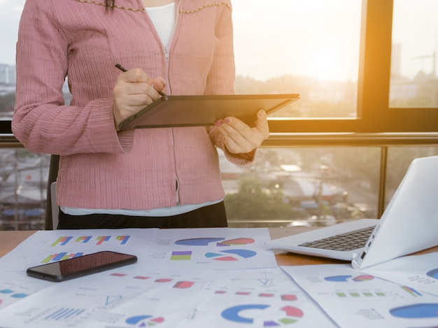Femme d'affaires analysant des graphiques avec des réseaux sociaux de technologie informatique