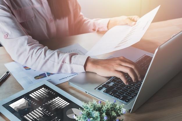 Femme d'affaires, analyse des graphiques d'investissement avec ordinateur portable sur la table de bureau.