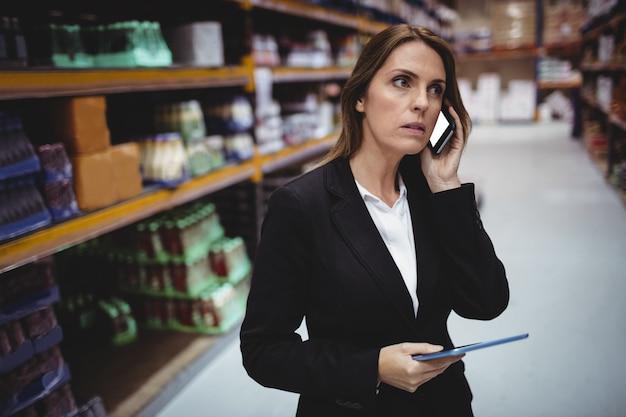Femme d'affaires sur un appel téléphonique en entrepôt