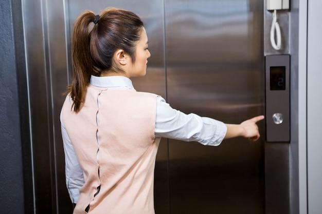 Femme d'affaires en appuyant sur le bouton d'ascenseur au bureau