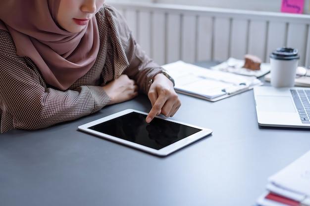 Femme d'affaires arabe en hijab brun travaillant avec tablette et ordinateur portable au bureau.
