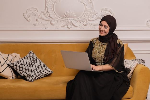 Femme d'affaires arabe travaillant sur ordinateur portable depuis la maison