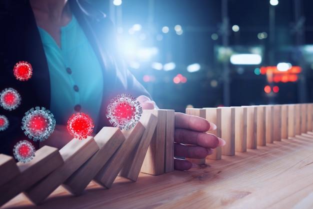 Femme d'affaires arrête une chute de chaîne par des virus comme un jeu de domino