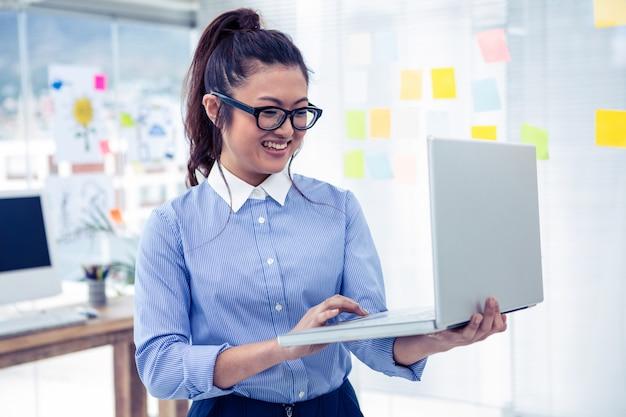 Femme d'affaires asiatique à l'aide d'un ordinateur portable au bureau